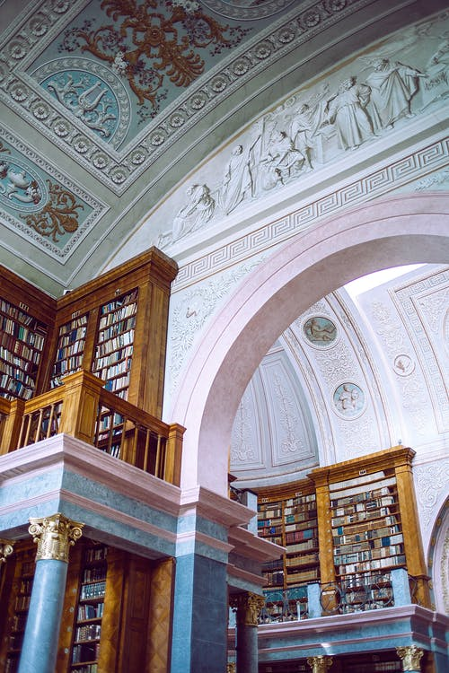 From below of aged building interior with decorative ceiling and walls near collection of literature on bookshelves