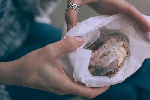 From above of crop unrecognizable person showing tasty sweet donut with glaze in organic bag on street