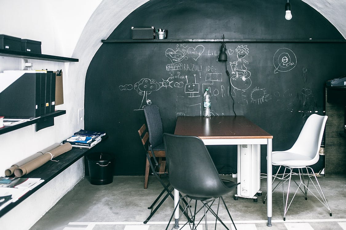 Blackboard with inscriptions and sketches near table with chairs on floor in light office room