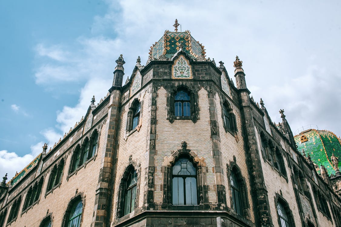 Low angle of old stone building facade with arched windows and ornamental walls in Hungary