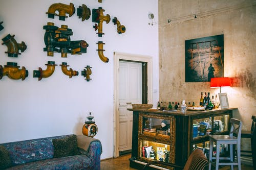 Comfortable retro styled room with metal pipes on wall near vintage table with various glass bottles