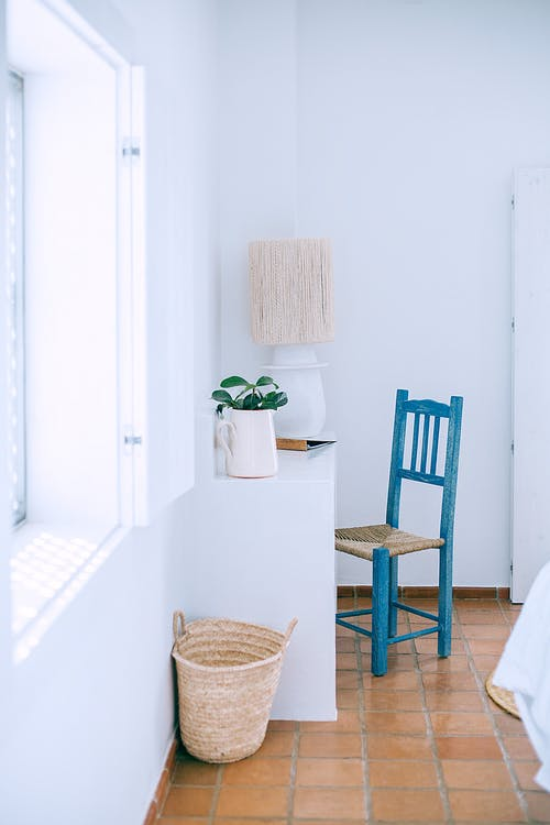 Interior of light room with window in white wall and old tiled floor