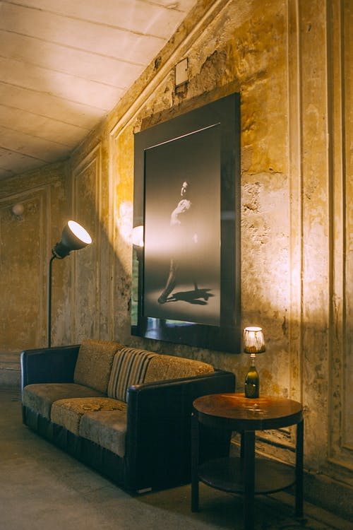 Interior of room with retro furniture and stone ornamental walls under uneven ceiling