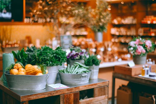 Assorted fresh vegetables and herbs in iron containers on table in modern store