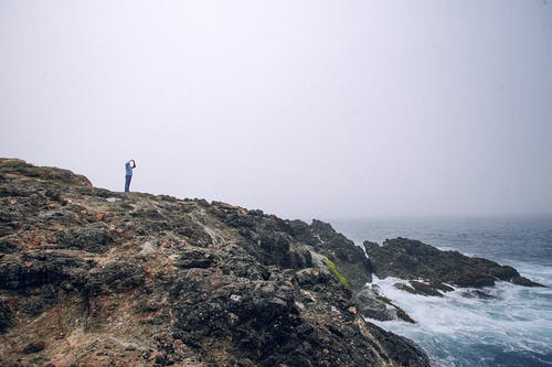 Distant anonymous person standing on rough rocky cliff near wavy ocean and taking photo in overcast weather