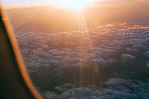 Through plane window of dark endless clouds under bright orange light of sun