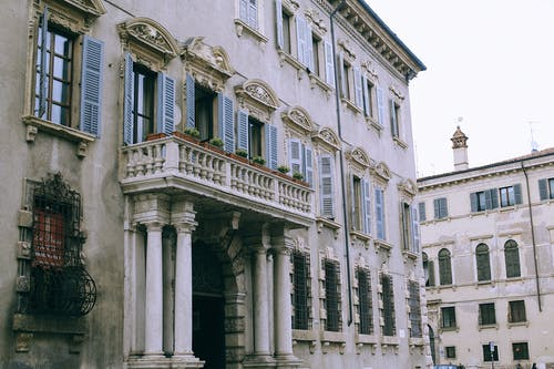 Facade of ancient classic building with balcony and columns located in old city