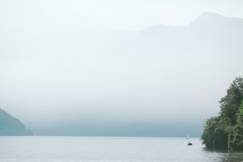 Boats on calm sea water against mountains