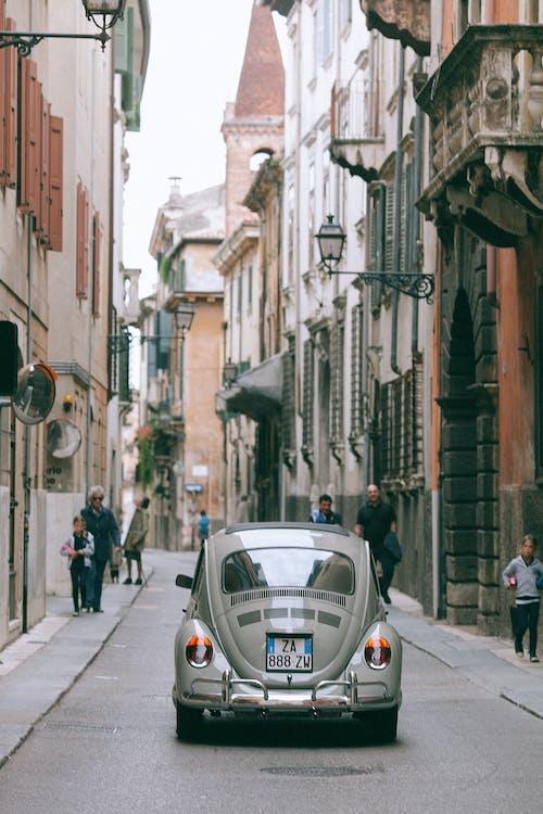 역사적인 도시에서 좁은 길을 따라 운전하는 레트로 자동차