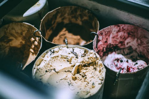 From above assorted steel buckets with appetizing ice creams with different flavors in cafeteria