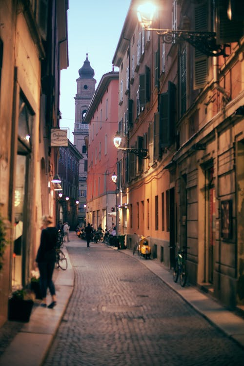 Pedestrian cobblestone street between historic stone buildings with streetlights in old European city in twilight
