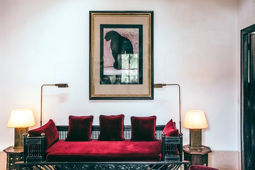 Comfortable couch with velvet red pillows between stylish lamps near creative painting on wall in light modern living room