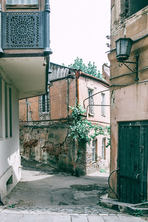Narrow pedestrian street between shabby residential buildings
