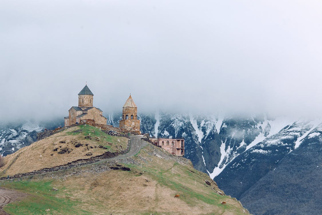 Medieval church on grassy hilltop surrounded by majestic mountains