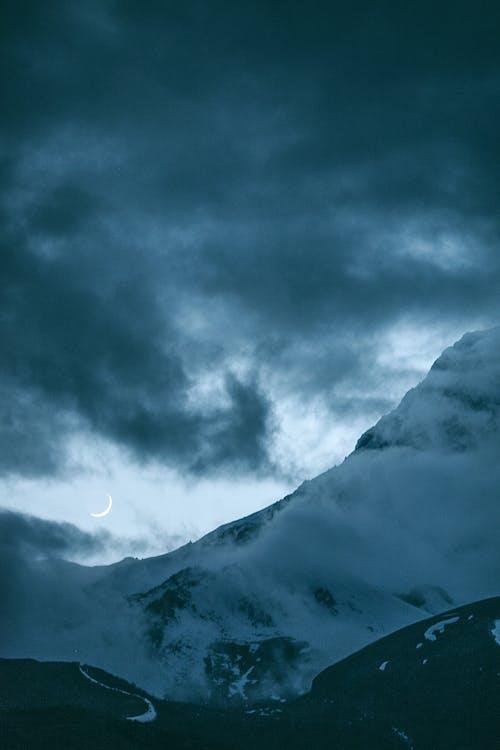 Luna Nueva Sobre Montañas Nevadas En La Noche Nublada