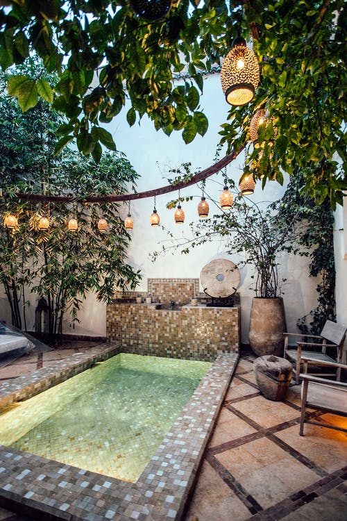 Traditional oriental hammam pool on exotic resort spa terrace decorated with lush plants  and stylish lanterns