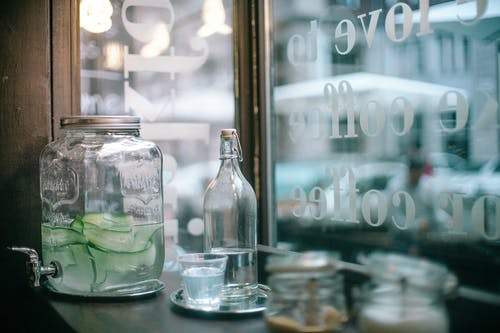 Glass jar of cucumber infuse water and bottle of mineral water with glass placed on wooden table with sugar jars located in urban cafeteria
