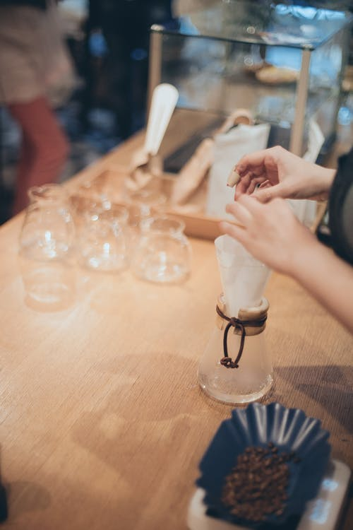 Faceless crop barista preparing coffee in cafeteria