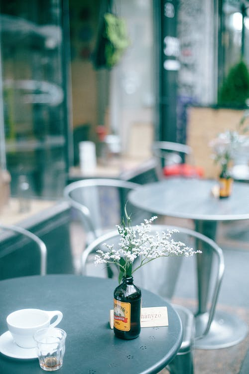 Table decorated with glass vase with fresh flowers and cup of drink located in outside cafeteria in daytime