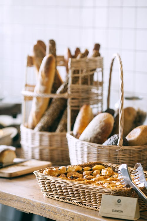 Tasty fresh homemade baguette placed in wicker basket and fresh baked pies in bakery in daytime