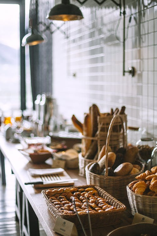 Side view of delicious fresh baked baguette and buns in wicker basket and fresh baked pies and croissant in bakery in daytime