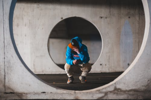 Full body male hipster in stylish clothes sitting on haunches and using phone in round passage of concrete basement