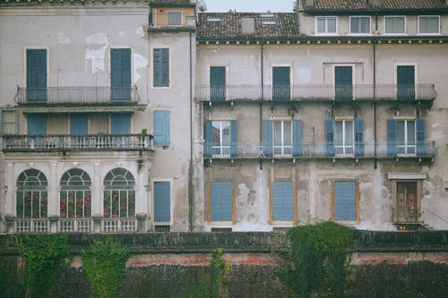 Shabby old building decorated and windows with balconies and fence with green plants in city in daytime