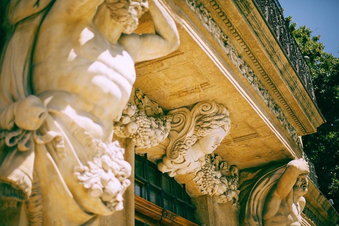 Ancient statues near entrance in old building