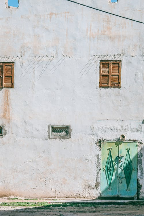 Aged building with wooden shutters on wall with white stucco and geometric decor on doors