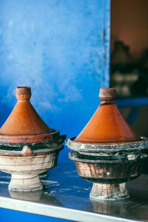 Traditional Moroccan heat resistant tajines with cone shaped covers and circular base on table