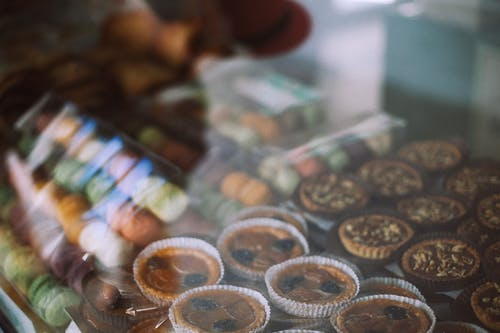 Through glass view of different tasty tartlets and macaroons for sale in sweet shop