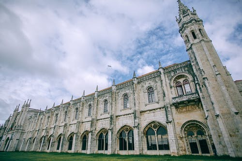 Facade of Jeronimos Monastery near lawn under cloudy sky