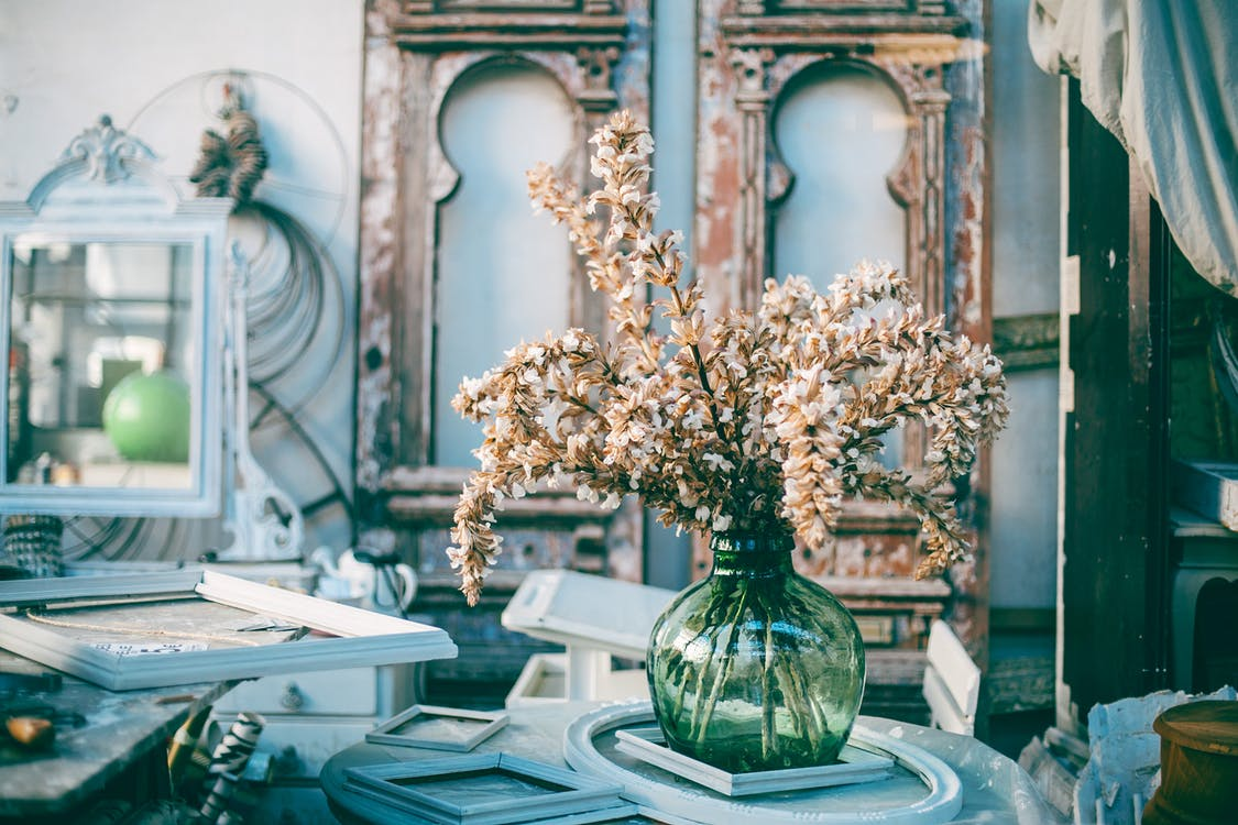 Bunch of delicate flowers in glass vase placed on table amidst various empty frames in stylish cozy art workshop