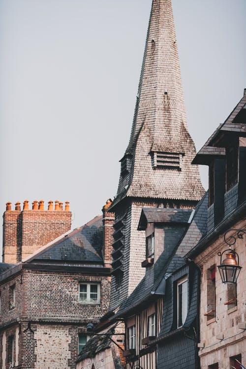 From below exterior of typical stone residential houses and historic Musee de la Marine located in Honfleur on sunny day