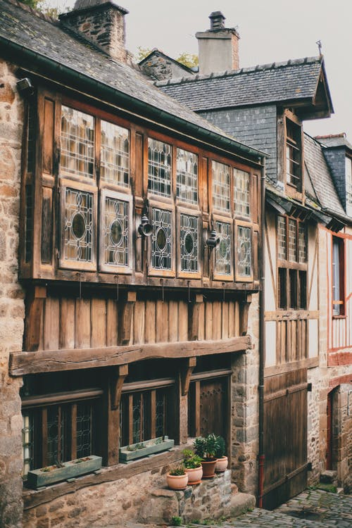 Facade of typical old stone residential houses with wooden windows and tiled roofs located on Rue de Jerzual narrow cobblestone street in medieval town of Dinan