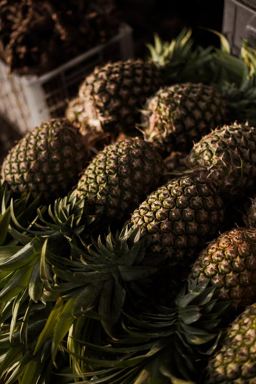 Ripe healthy pineapples arranged in street grocery store