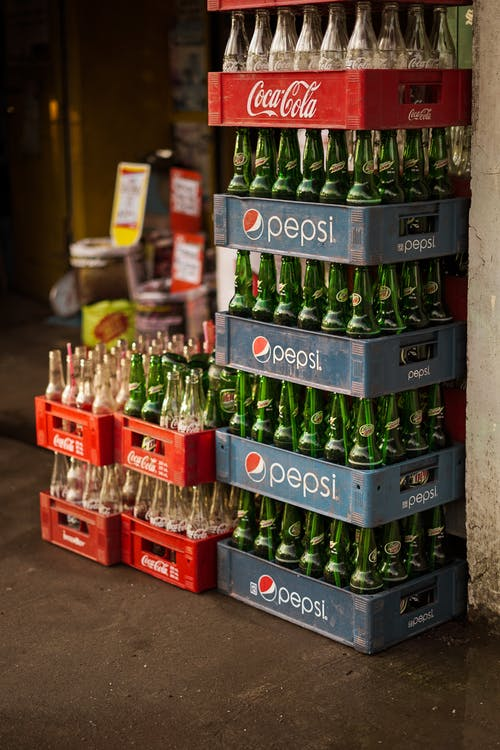 Glass bottles of coke and beer in various containers placed on ground on town street near rustic market