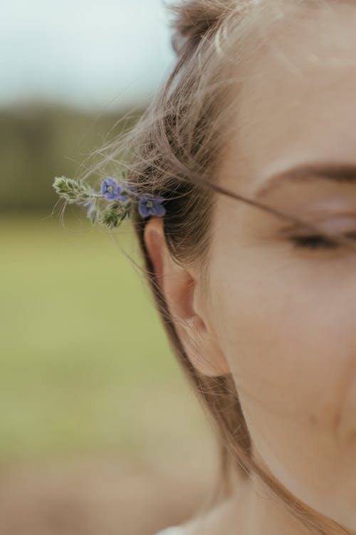 Woman With Blue Flower on Ear