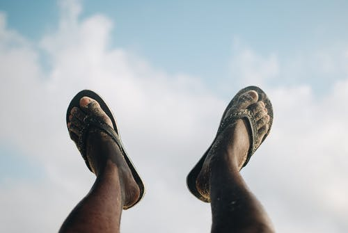 Person Wearing Black and White Flip Flops
