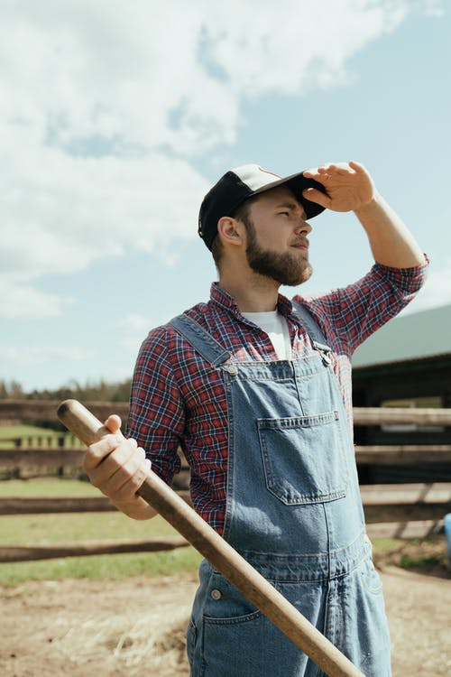 Man in Blue Denim Button Up Shirt and Black Hat Holding Brown Wooden Stick