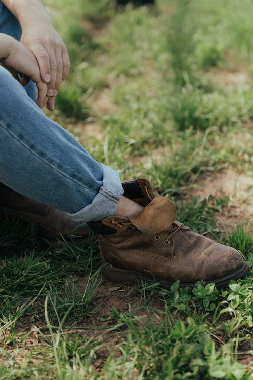 Person in Blue Denim Jeans and Brown Leather Boots Sitting on Green Grass