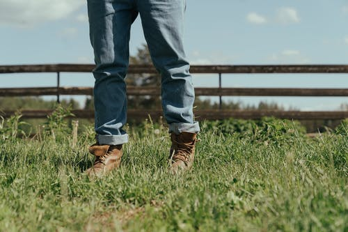 Person in Blue Denim Jeans and Brown Leather Boots Standing on Green Grass Field