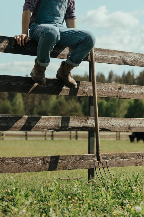 Person in Blue Denim Jeans and Brown Boots Sitting on Brown Wooden Fence