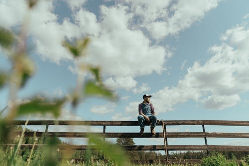 Girl in Pink Jacket and Blue Denim Jeans Sitting on Brown Wooden Fence Under White Clouds