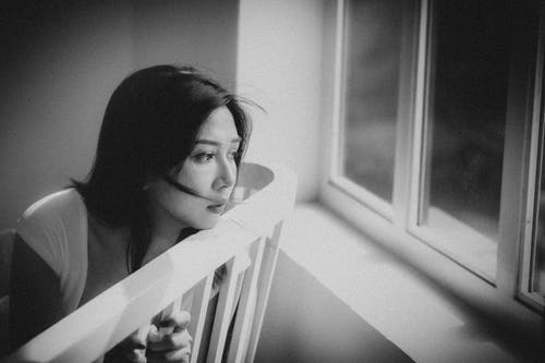 Sad Asian woman looking out window