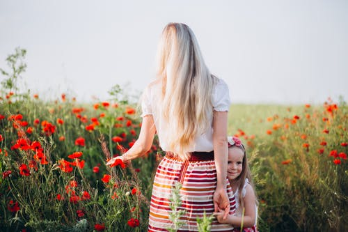 Cheerful girl holding hand of faceless mother in field
