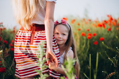 Positive girl holding hand of mother in floral field