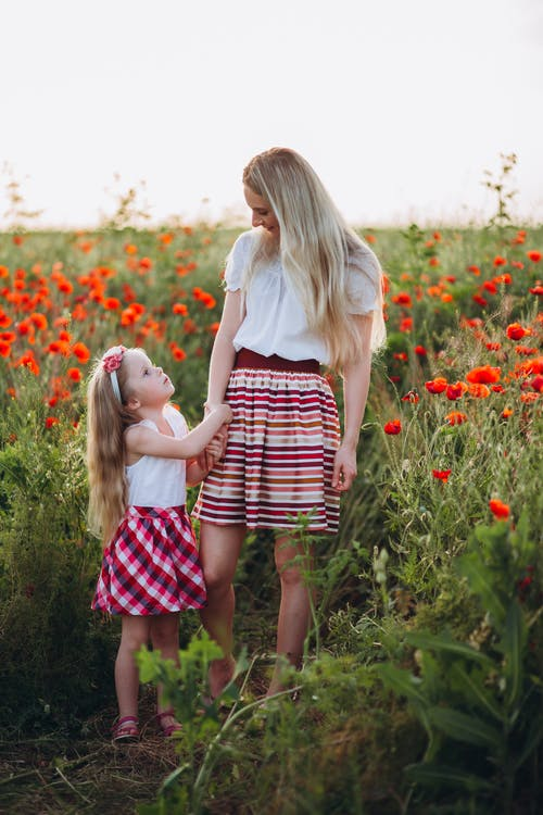 Mother and daughter in field of flowers in summertime