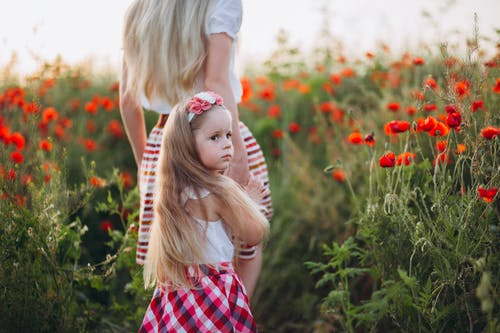 Pensive little girl holding hand of mother in field