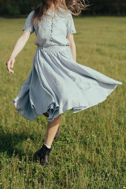 Girl in White Dress Walking on Green Grass Field
